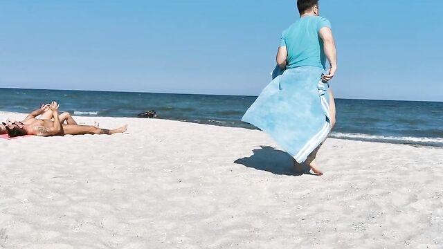 Два парня и девушка устроили групповой секс на нудистском пляже